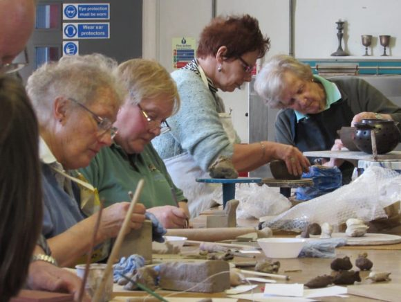 A group of five people working at a bench in a ceramics workshop
